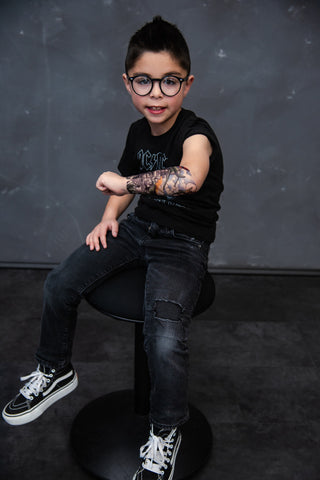 Little boy showing off his military themed temporary tattoo on his forearm.