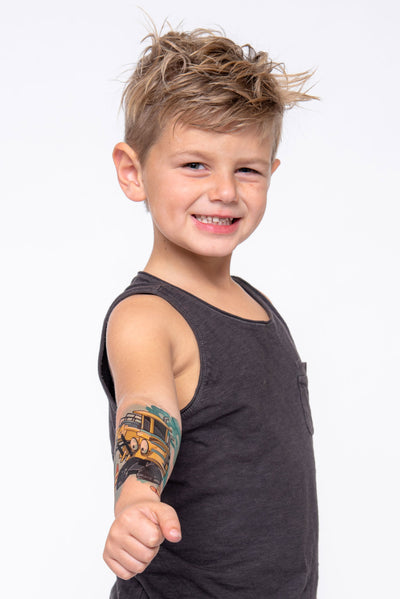 Young boy shows off his forearm temporary tattoo sleeve with construction equipment.