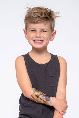 Front view of young boy wearing construction temporary tattoo sleeve on lower arm.