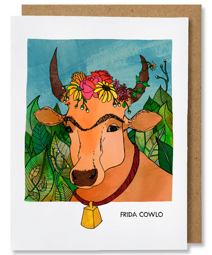 The Frida Cowlo greeting card depicts a portrait of Frida Kahlo as a tan cow with a unibrow and flowers along the top of her head between her horns. A vine with a flower twirls its way up the right-side horn. The cow is also wearing a cow bell that hangs on a red collar. The cow is in front of a wall of lush, green foliage and blue sky. This card is placed with a brown kraft envelope.