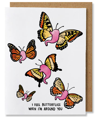 I Feel Butterflies is a white ground greeting card that features5 pink stomachs with yellow and orange butterfly wings. The words beneath say
