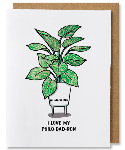 I Love My Philo-dad-ron is a white ground greeting card that features a philodendron birkin plant potted in a white planter with legs. The words beneath say
