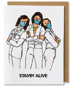"Stayin' Alive - White ground greeting card featuring The Bee Gees in white outfits wearing blue masks, standing shoulder to shoulder. The words ""stayin' alive"" is written below them"