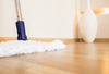A white microfiber mop cleaning light colored hardwood flooring.