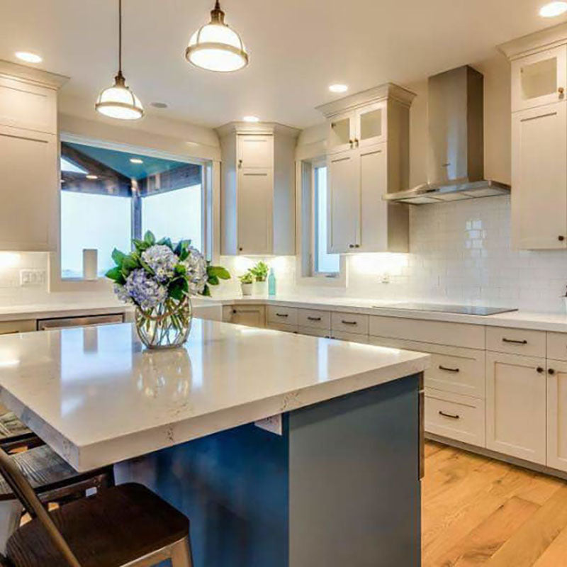 A renovated kitchen with white cabinets and natural hardwood flooring from Standard Paint & Flooring.