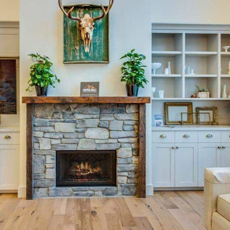 A fireplace with natural large stones, with white cabinets and natural hardwood flooring by Standard Paint & Flooring.