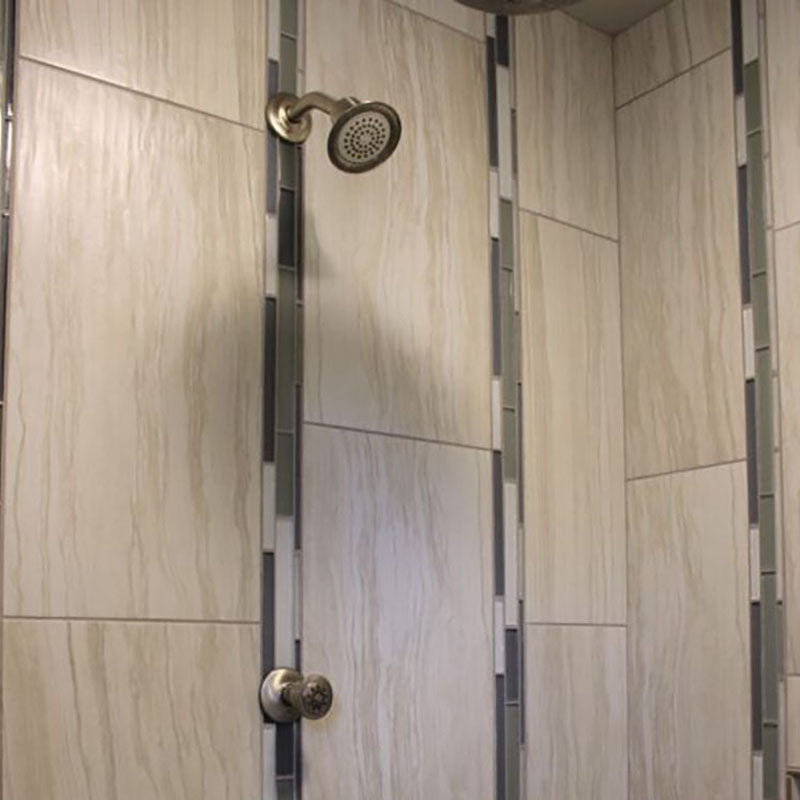 Close up view of inside a renovated shower with a tile wall design from Standard Paint & Flooring.
