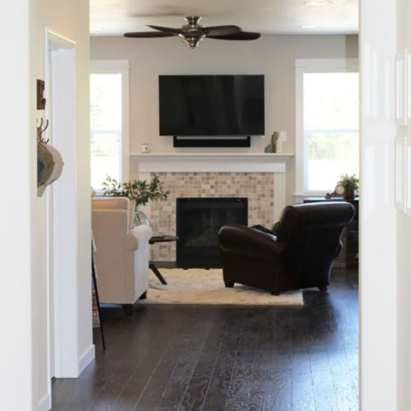 View from a hallway looking into a living room with dark laminate flooring, a plush beige area rug, and a fireplace with a tile design on the front, all from Standard Paint & Flooring.