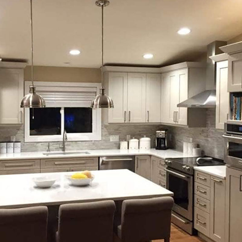 A kitchen with white cabinets and light grey backsplash tile from Standard Paint & Flooring, stainless steel appliances and an island with a white top.