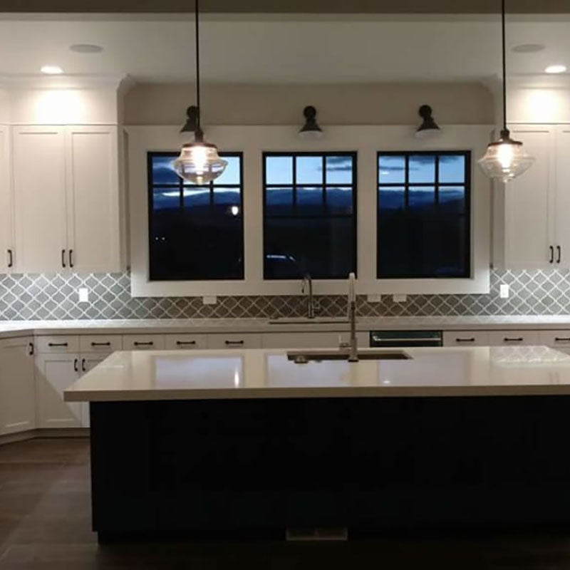 A renovated kitchen designed by Standard Paint & Flooring, with white cabinets and a grey and white accent back splash tile, with a kitchen island with white marble countertop and dark wood siding.
