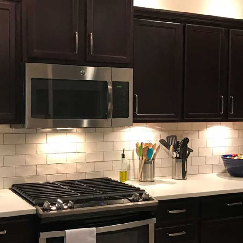 Dark wooden kitchen cabinets with white subway tile backsplash from Standard Paint & Flooring and a stainless steel stove and microwave above the stove.