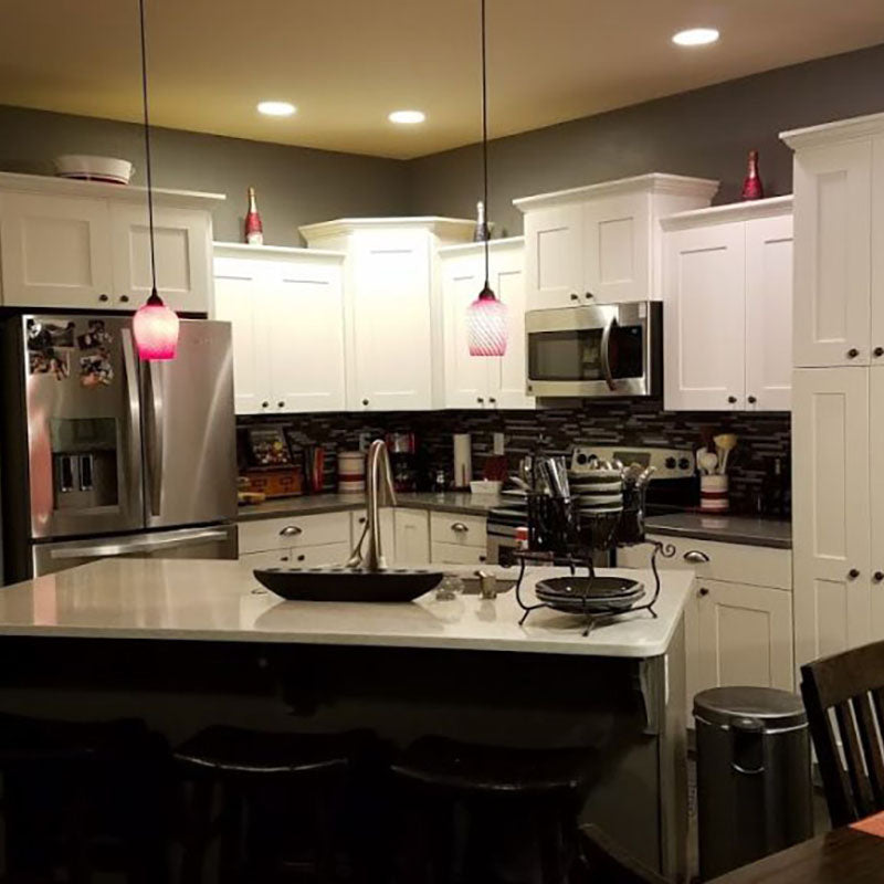 A kitchen with white cabinets and dark accent backsplash tile and hanging light fixtures from Standard Paint & Flooring, with a stainless steel fridge, stove and microwave.