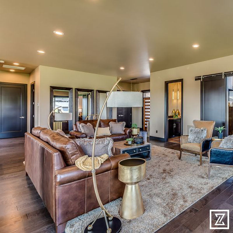 A living with hardwood flooring, a beige plush area rug, with brown leather furniture, designed by Kate Loeb, Designer at Standard Paint & Flooring.