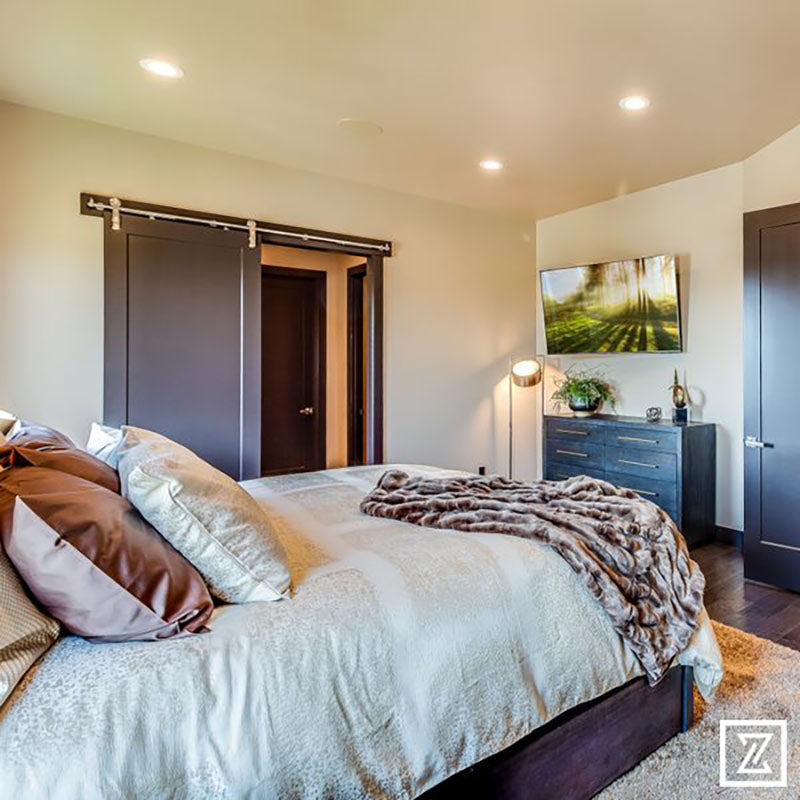 A bedroom with hardwood flooring, a plush area rug under a king sized bed with beige and gold blankets and pillows, with dark wood barn style doors on the closet, designed by Kate Loeb, Designer at Standard Paint & Flooring.
