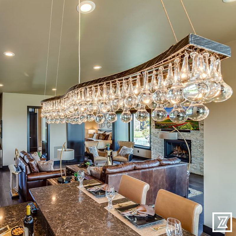 View from above a kitchen island with a granite countertop, light brown leather chairs and a large hanging light fixture, all designed by Kate Loeb, Designer at Standard Paint & Flooring.