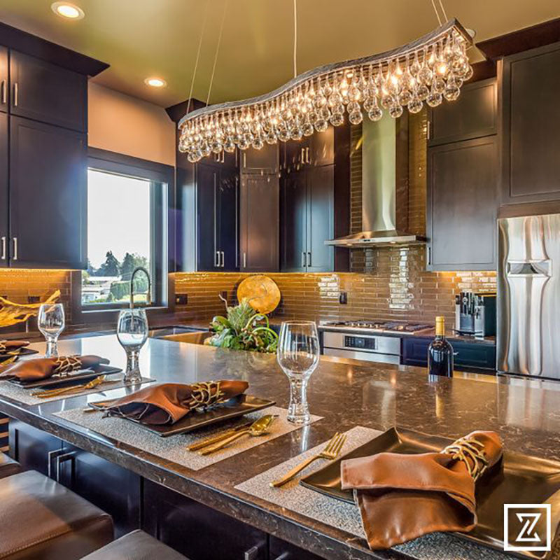 A kitchen island with a granite countertop with dark kitchen cabinets and a large hanging light fixture, all designed by Kate Loeb, Designer at Standard Paint & Flooring.