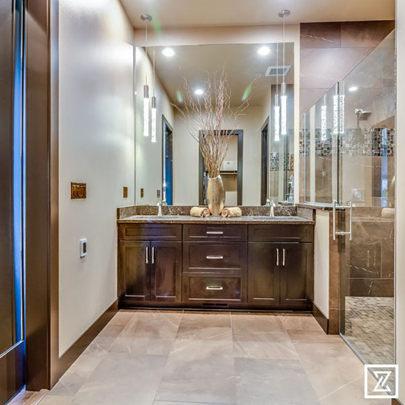 A bathroom with dark brown cabinets, marble countertop and large mirror, with light brown ceramic tile from Standard Paint & Flooring.