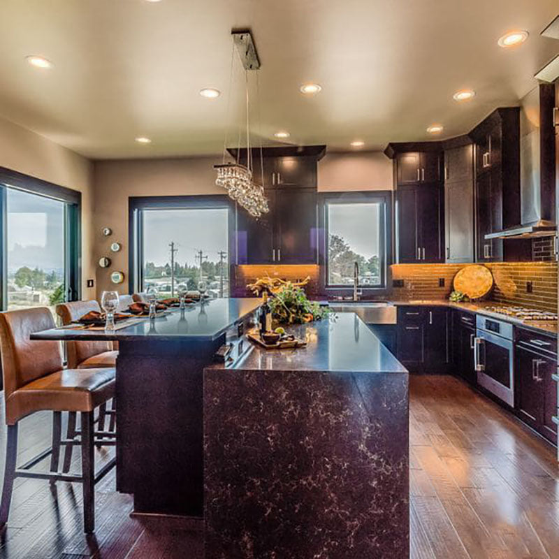 View from the side of a granite kitchen island with light brown leather chairs, with a large lighting fixture hanging above and dark kitchen cabinets, designed by Kate Loeb, Designer at Standard Paint & Flooring.
