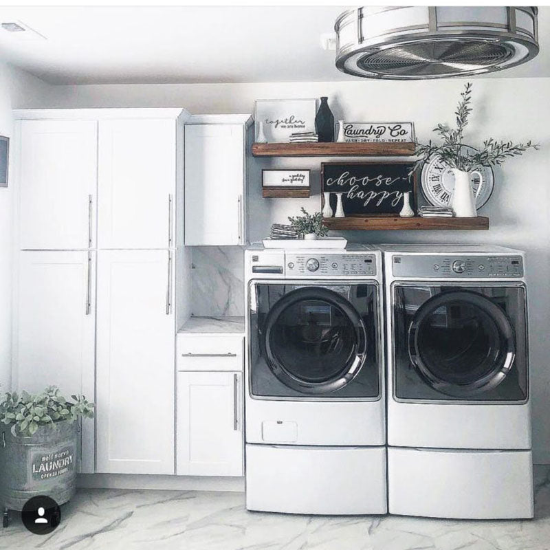 A renovated laundry room by Standard Paint & Flooring, with white storage cabinets and marble tile flooring.