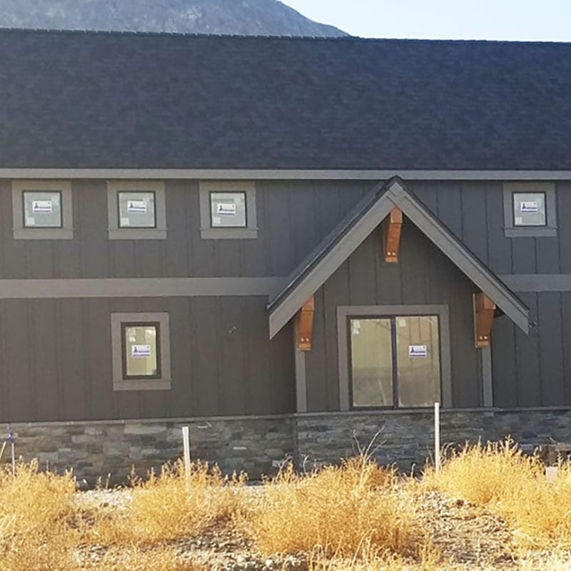 Exterior of a freshly painted barn style building with dark grey paint from Standard Paint & Flooring.