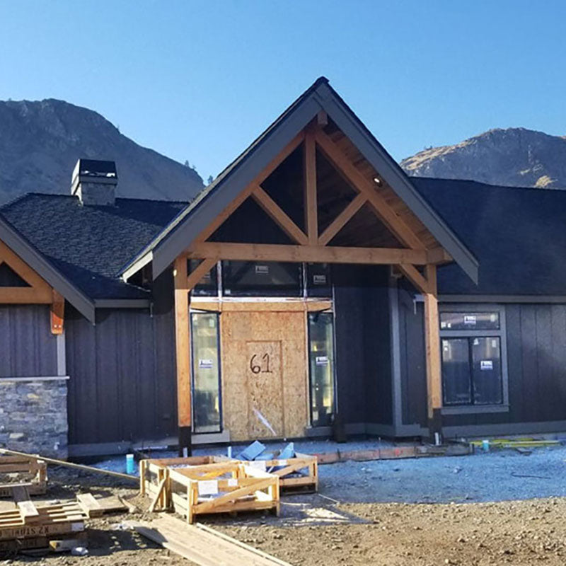 Exterior of a house being built with dark grey paint from Standard Paint & Flooring.