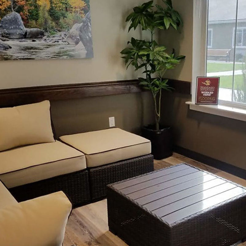 A waiting room with a couch with large beige cushions and new laminate flooring by Standard Paint & Flooring.