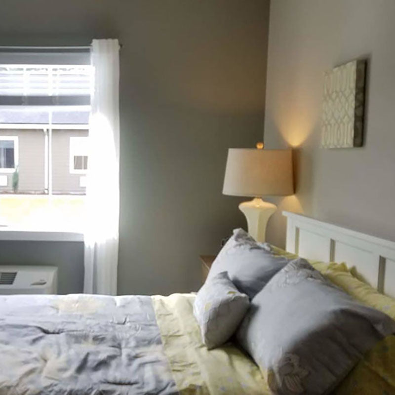 A bedroom painted grey with paint from Standard Paint & Flooring, with a bed with grey and yellow blankets and pillows.