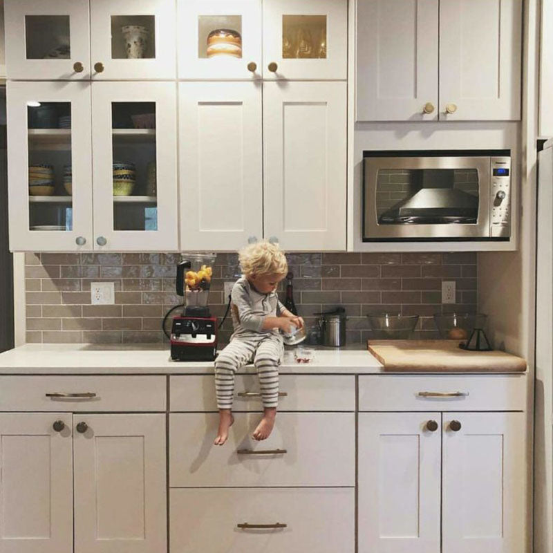 White kitchen cabinets from Standard Paint & Flooring with a light brown back splash tile and a young child sitting on the kitchen counter.