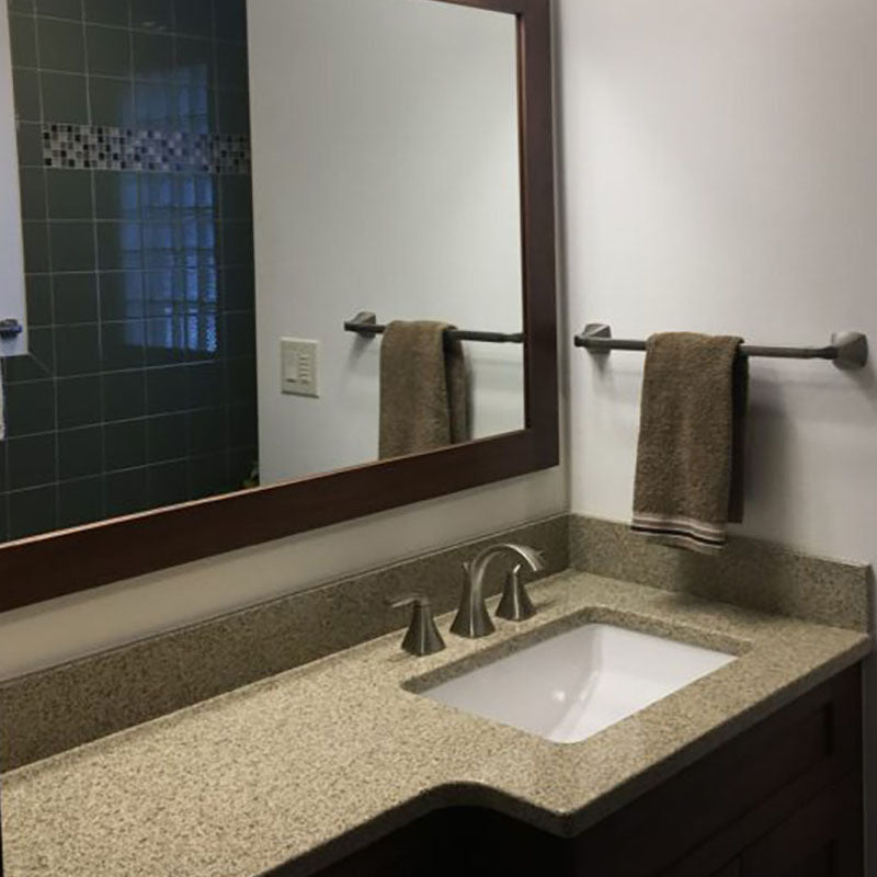 A renovated granite bathroom countertop and mirror with dark wooden trim, by Standard Paint & Flooring.