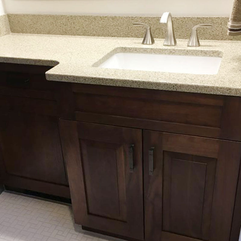A renovated granite bathroom countertop with dark wood cabinets and small white tiled flooring, by Standard Paint & Flooring.