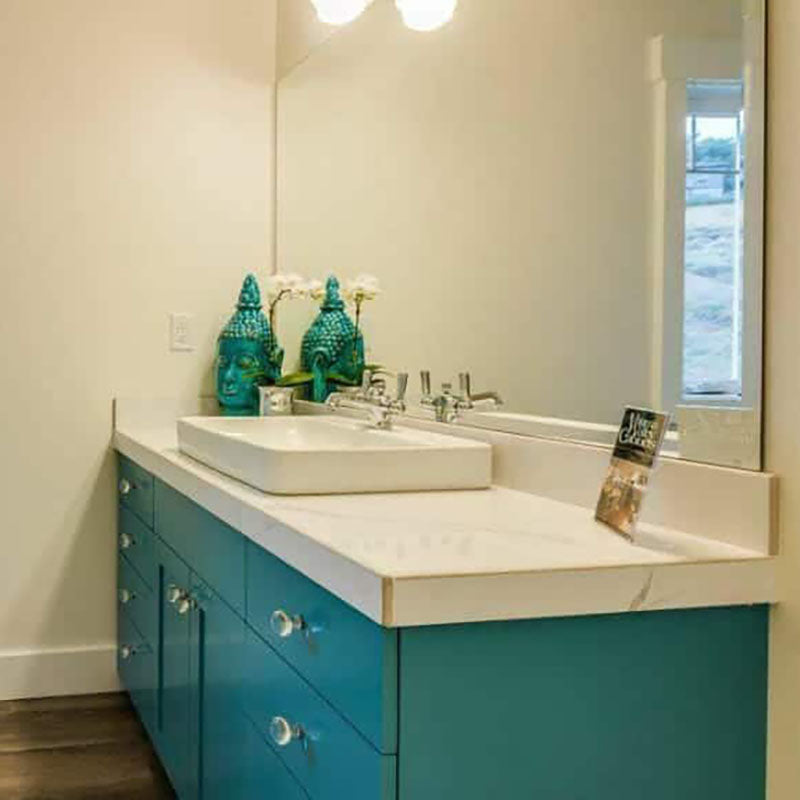 A bathroom vanity with turquoise cabinets by Standard Paint & Flooring, with a white marble countertop and white porcelain sink above the counter.