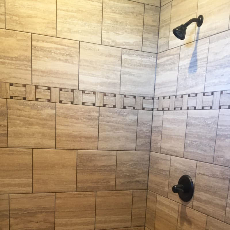 Close up view of inside a shower with a brown ceramic tile design from Standard Paint & Flooring.