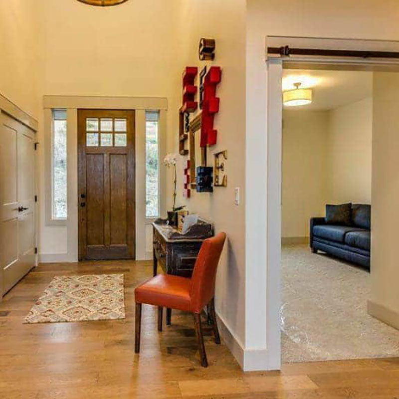 View of an entrance of a home with natural hardwood flooring by Standard Paint & Flooring, a dark wood front door and a patterned carpet.