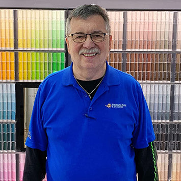Dave Shrewsberry smiling in front of a wall of paint color chips at Standard Paint & Flooring's Sunnyside, WA location.