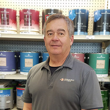 Dean Evans smiling in front of Benjamin Moore paint cans at Standard Paint & Flooring's Downtown Yakima location.