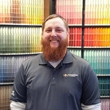 Dylan Eskeli standing in front of a wall of paint color chips at Standard Paint & Flooring's Richland, WA location.