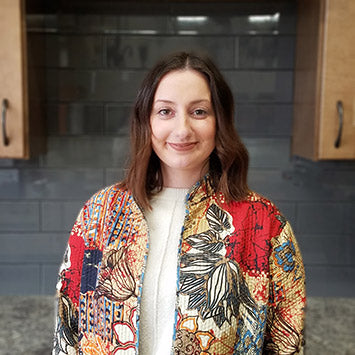Emily Hunter smiling in front of wooden cabinets at Standard Paint & Flooring's Downtown Yakima location.
