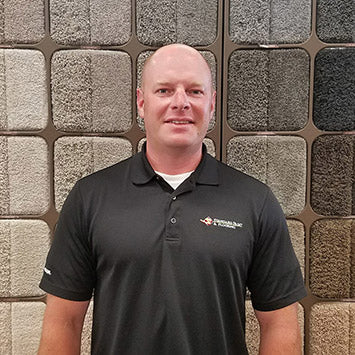 Jared Jenkins wearing a black polo shirt smiling in front of the Shaw Carpet Wall at Standard Paint & Flooring's West Valley Yakima location.