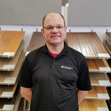Jeff Rock wearing a black polo shirt and standing in front of hardwood flooring at Standard Paint & Flooring's West Valley Yakima, WA location.