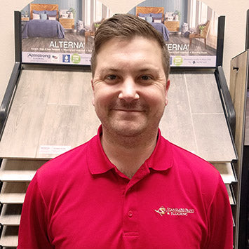 John Whitehead wearing a red polo shirt, smiling in front of laminate flooring at Standard Paint & Flooring's Downtown Yakima location.