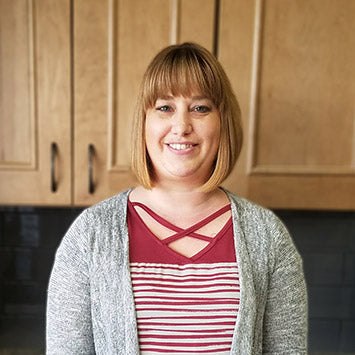 Lisa Helgelson wearing a white and red striped top, smiling in front of wooden cabinets at Standard Paint & Flooring's Downtown Yakima location.