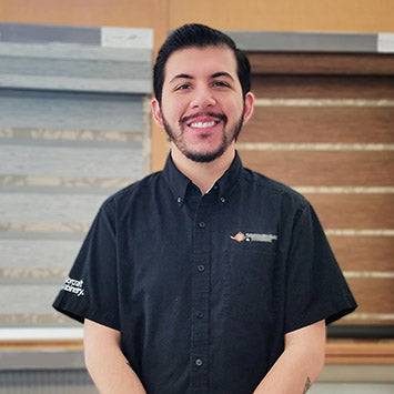 Marcus Flores smiling in front of the Window Treatments section at Standard Paint & Flooring's West Valley Yakima location.