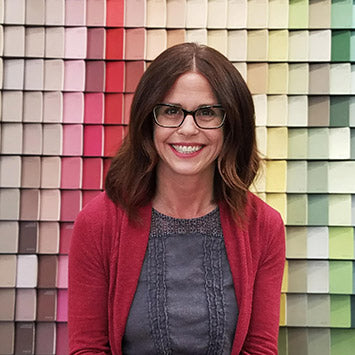 Marissa Tegen smiling in front of a wall of paint color chips at Standard Paint & Flooring's West Valley Yakima location.