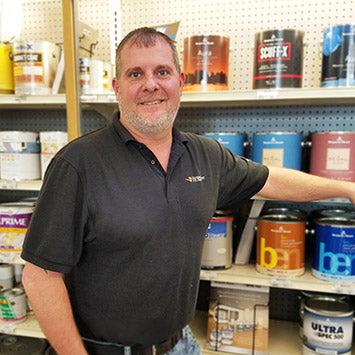 Michael Alred wearing a black polo shirt, standing in front of Benjamin Moore paint cans at Standard Paint & Flooring's Downtown Yakima, WA location.