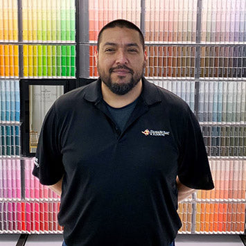 Mike Zavala smiling in front of a wall of paint color chips at Standard Paint & Flooring's Sunnyside, WA location.
