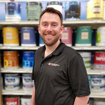 Nate Andreasen smiling in front of Benjamin Moore paint cans at Standard Paint & Flooring's West Valley Yakima location.