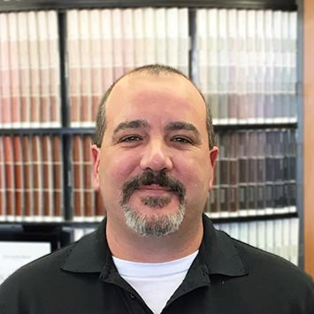 Patrick Otis smiling in front of a paint color chip wall at Standard Paint & Flooring's Bend, OR location.