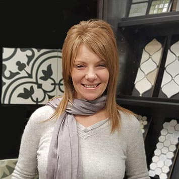 Phaedra Palomo smiling in front of accent tile swatches at Standard Paint & Flooring's Richland, WA location.