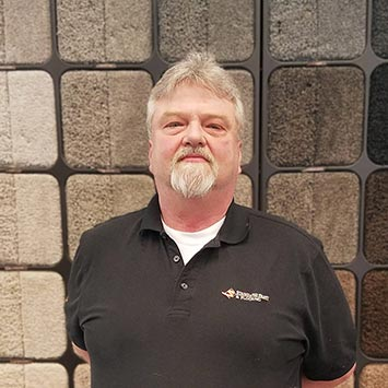 Randy Stuber smiling in front of the Shaw carpet wall at Standard Paint & Flooring's Wenatchee, WA location.