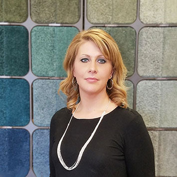 Sarah Fraijo smiling in front of the Shaw carpet wall Standard Paint & Flooring's Richland, WA location.